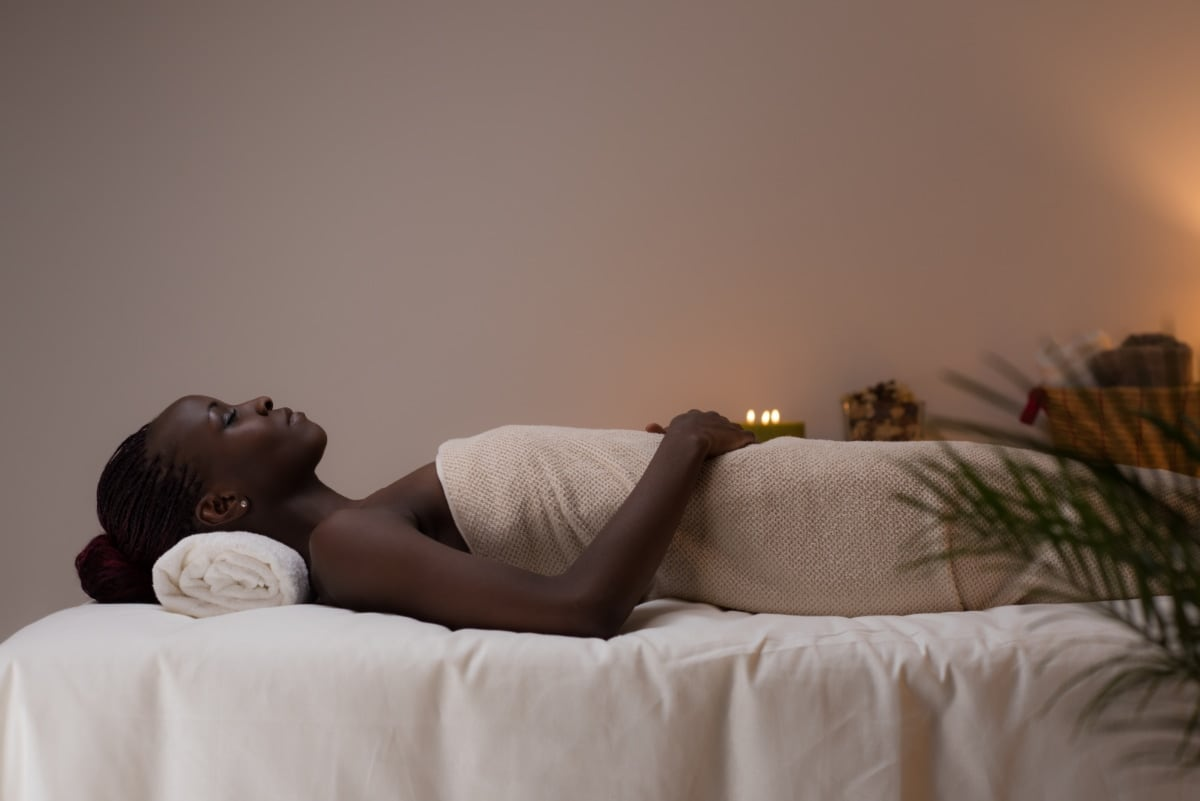 Woman laying on bed about to receive mobile massage therapy at home