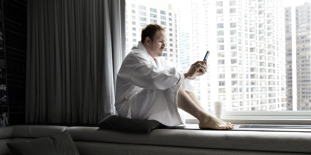 Lonely man, wearing gown, booking a massage on mobile phone