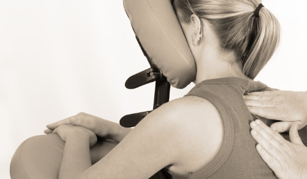 Office massage visiting service - with a woman receiving a shoulder massage whilst seated on a chair