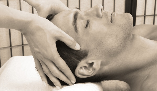 Mobile massage therapist giving a man a relaxing head massage